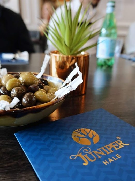 Juniper Hale menu bowl of olives rose gold plant