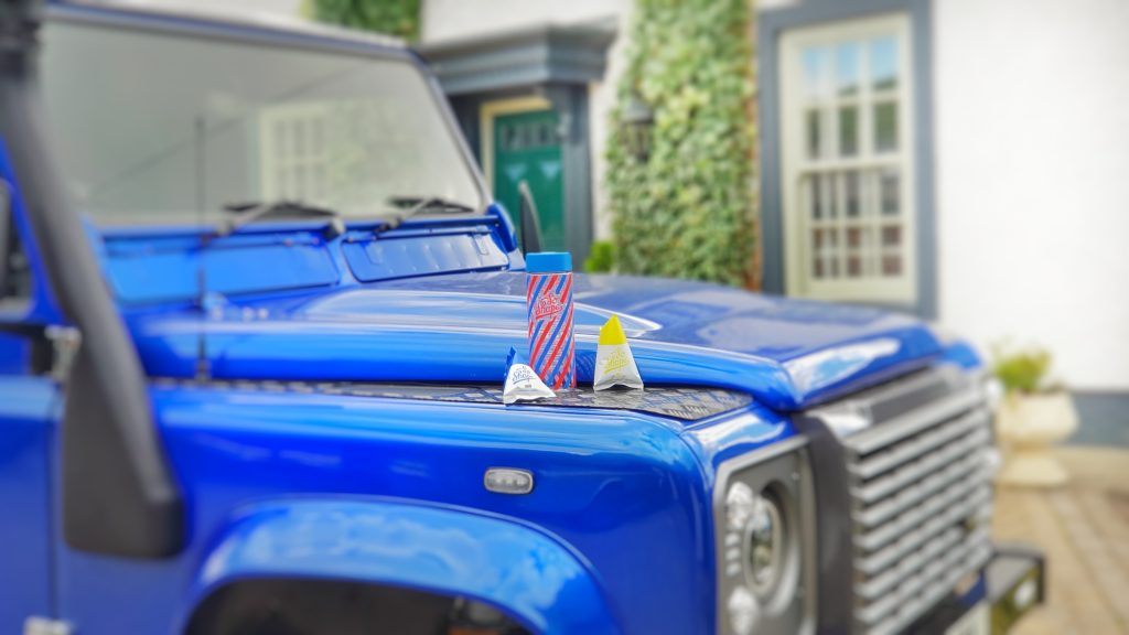 Blue Jeep with SoShape Flask and Protein Shake pouches on the bonnet