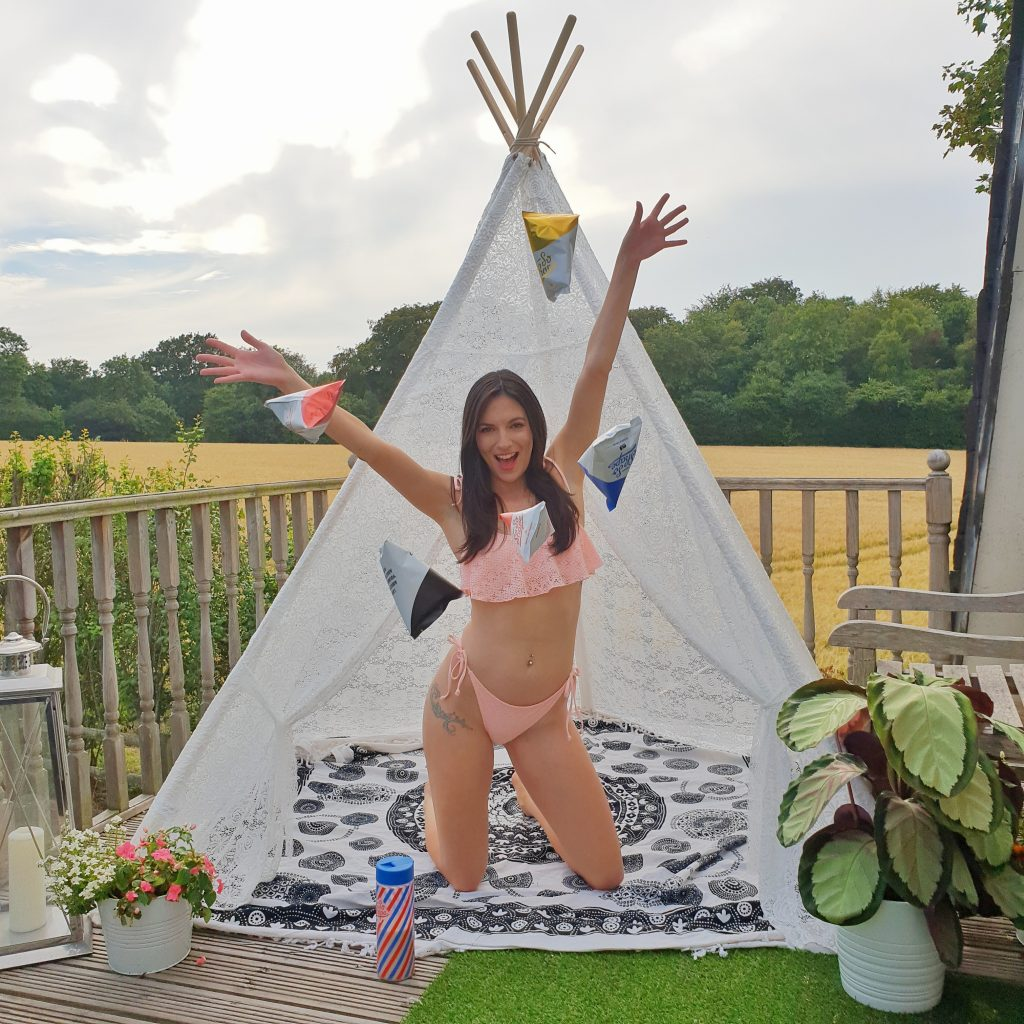 Missy wearing pink bikini throwing SoShape protein shake pouches out of lace teepee
