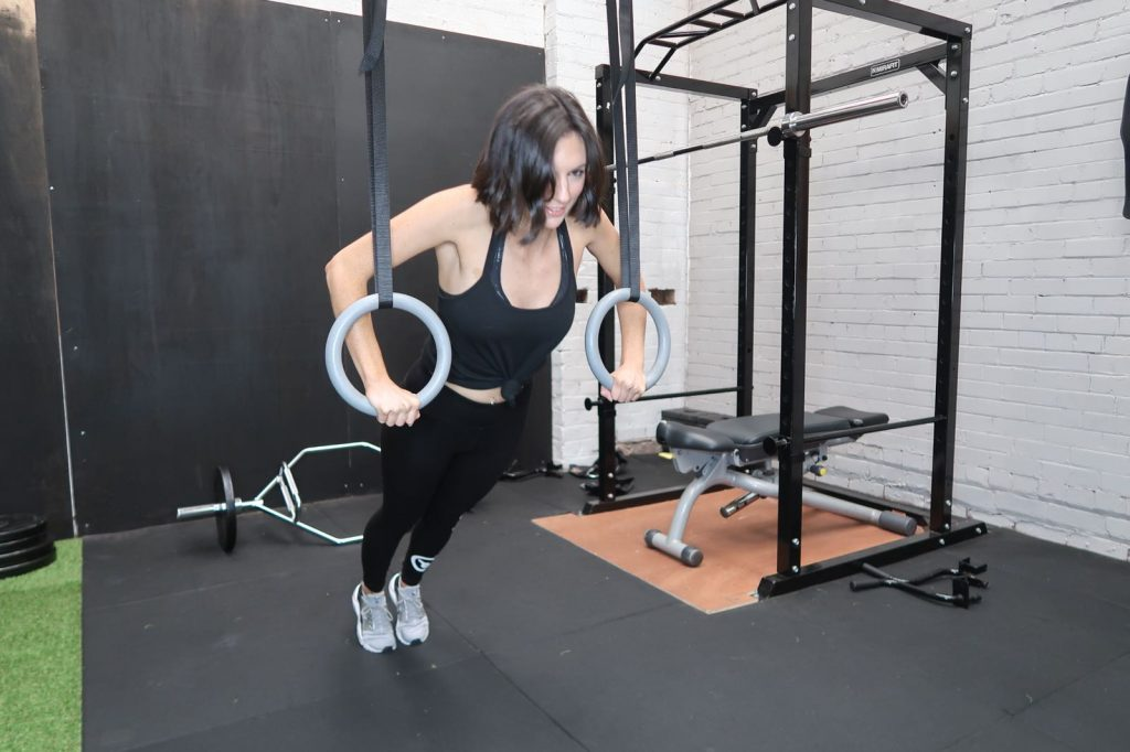 Personal Trainer exercising her chest on the olympic rings