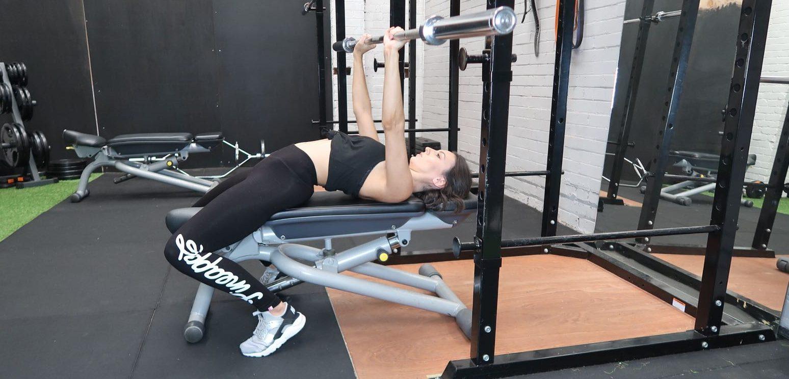 Girl Bench Pressing in gym