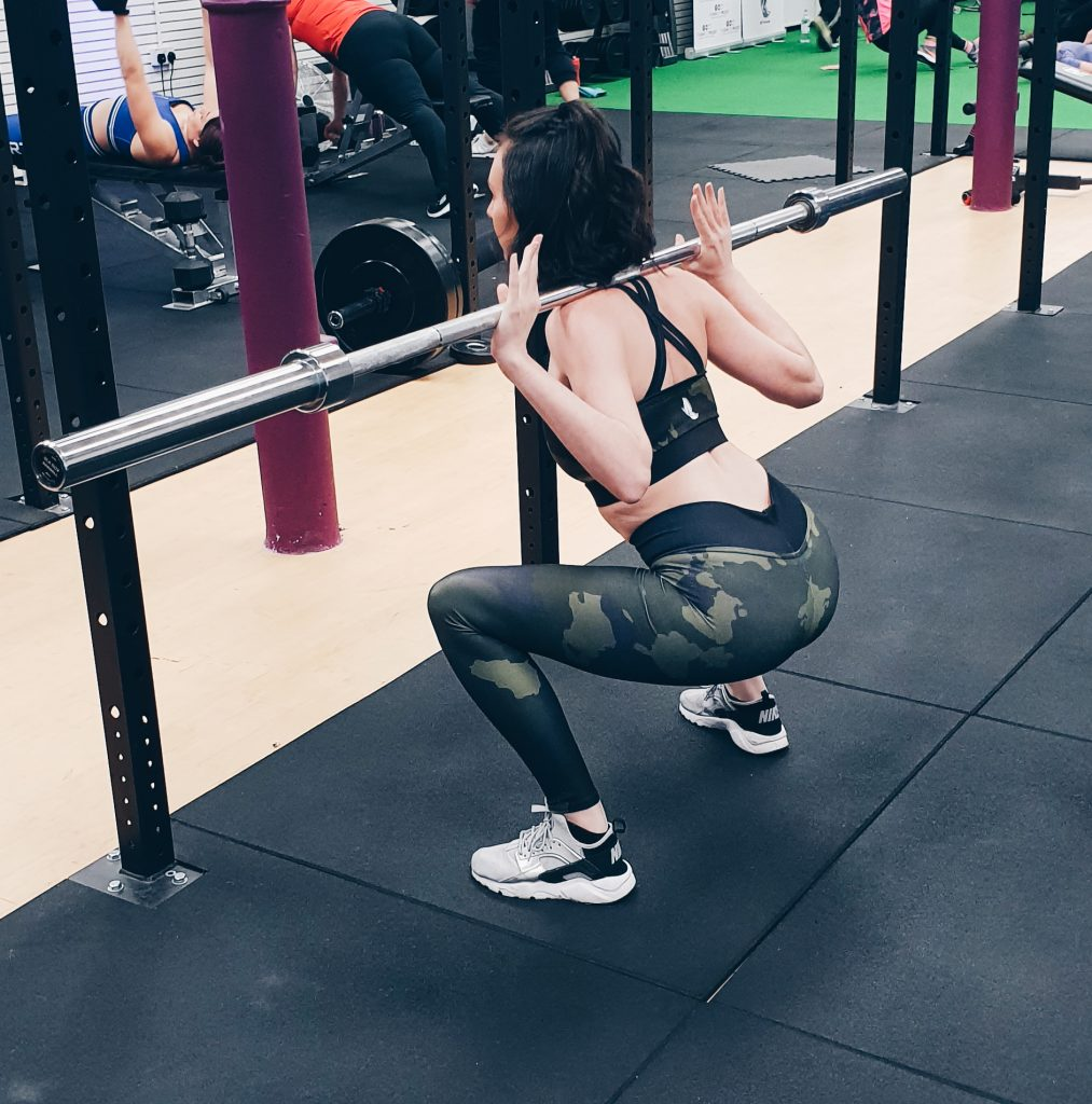 Personal Trainer Performing Squat Proof Test on HD Female leggings