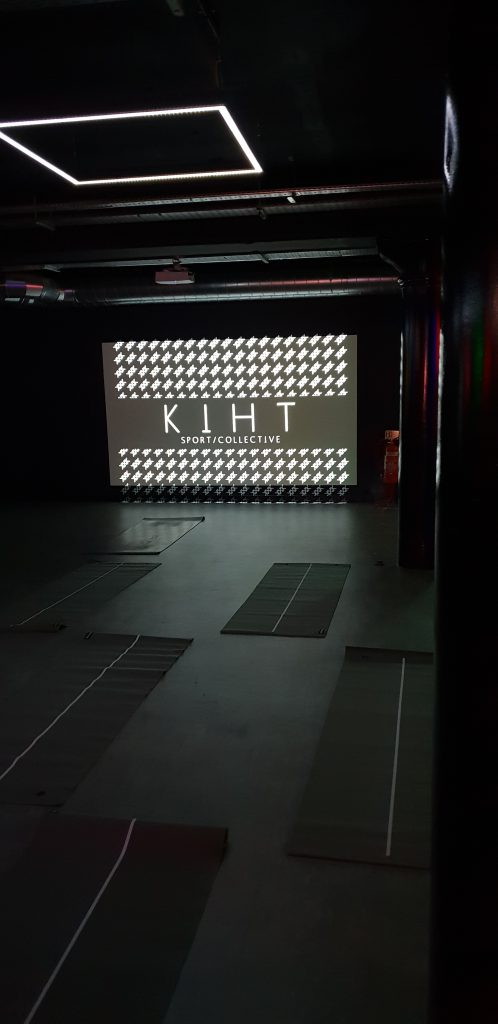 Pitch black room set up for the yoga class with KIHT Collective logo on screen.