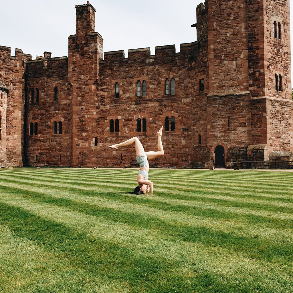 Personal Trainer Missy doing a headstand on the lawn outside Peckforton Castle after the Yoga Session wearing NEU Apparel Gymwear